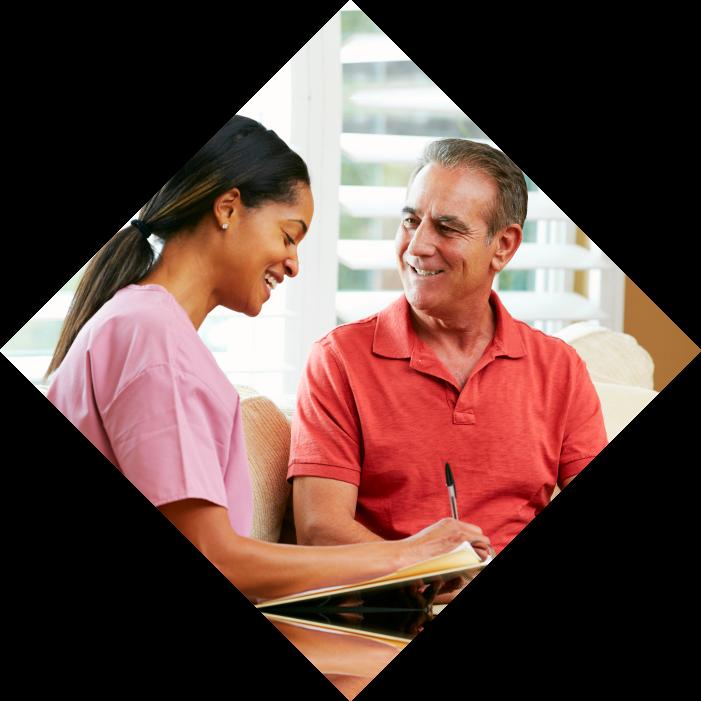 Man smiling and female caregiver writing